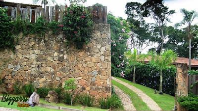 Muro de pedra construído com pedra moledo com o peitoril de dormente em cima.