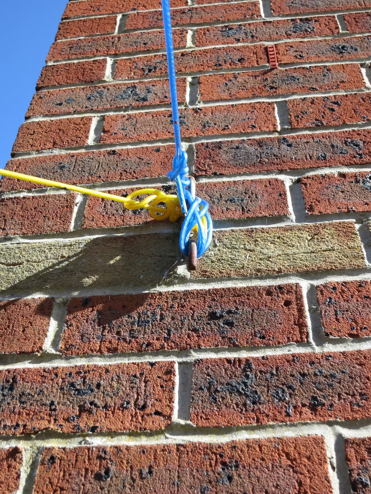 Washing lines, yellow and blue, wound round bracket on brick wall of house.