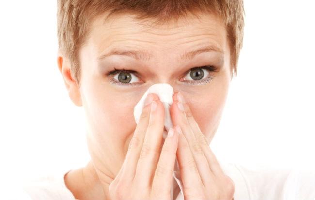 Donna raffreddata che si soffia il naso