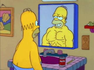 Homer Simpson se mira delante de un espejo imaginándose más cachas de lo que realmente está