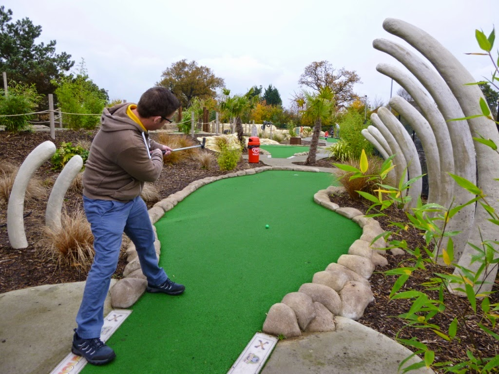 Richard Gottfried playing a shot through the remains of a dinosaur at Jungle Island Adventure Golf at Horton Park Golf Club in Epsom, Surrey