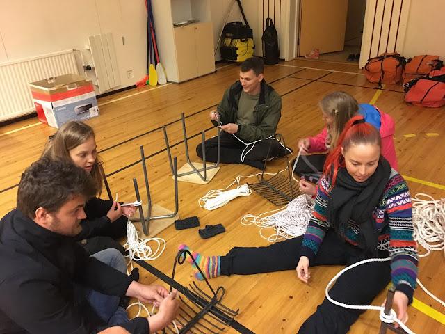 Lattialla istuu henkilöitä opettelemassa solmujen tekemistä