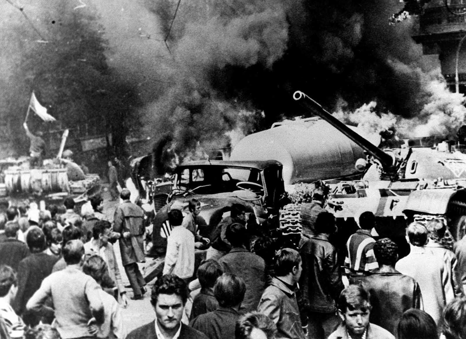 A Soviet tank, burning vehicles, and sullen citizens are seen in Prague on August 21, 1968, as Soviet troops entered the Czechoslovakian capital.
