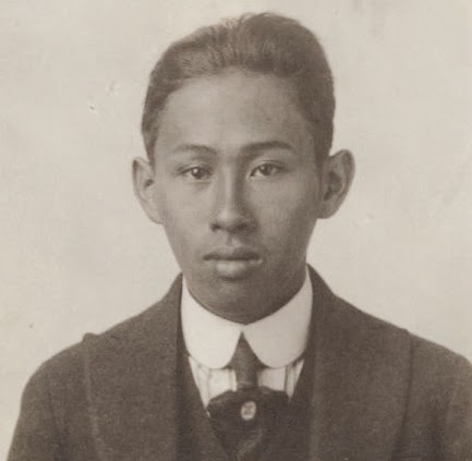 A black and white photo of Chu Hing shows him looking directly into the camera. He wears his hair short and is clad in a suit and tie with a pin.