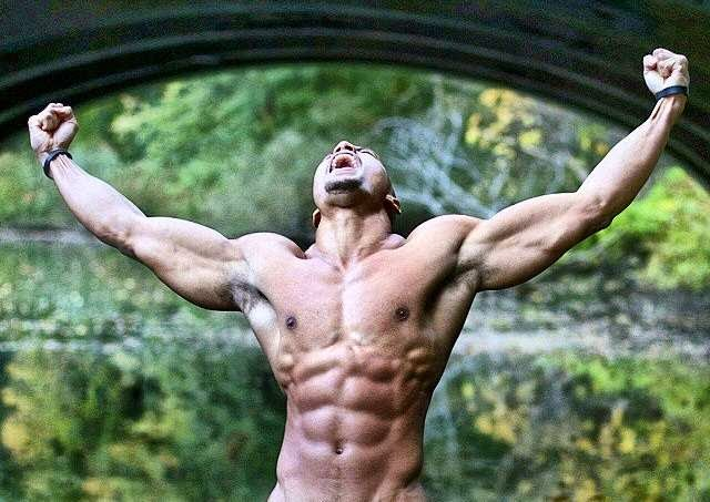 hombre musculoso sin camiseta gritando con los brazos abiertos