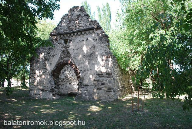 A kövesdi templomrom nyugati homlpkzata az egykori román stílusú bejárattal ligetes környezetben.