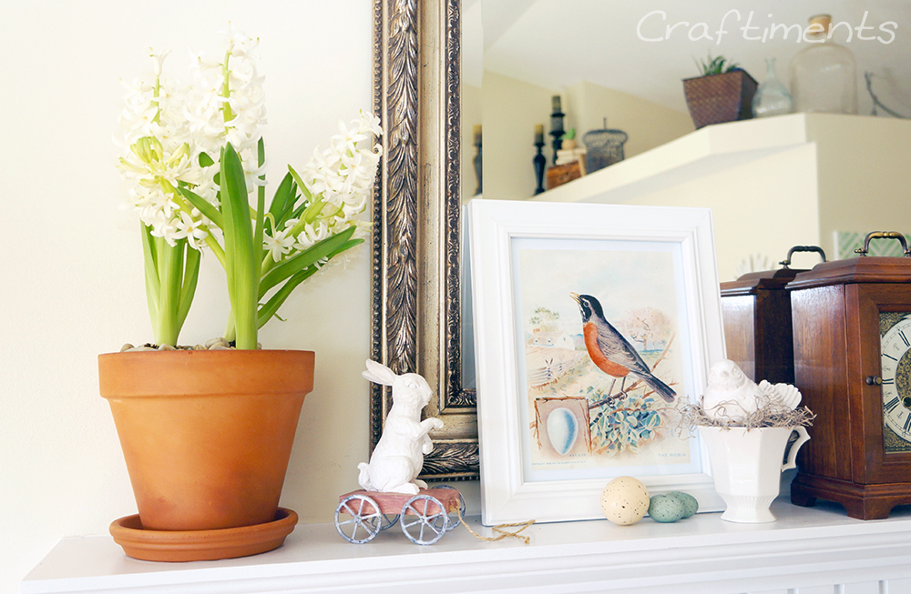 Spring mantel with flowering hyacinth bulbs, rabbit figurine, vintage robin art, and bird nesting in a teacup