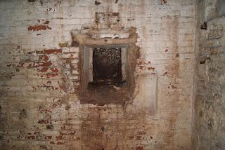 Ein rechteckiges Loch in einer weiß-braunen Wand. Das Loch ist mit einer Metallplatte verschlossen