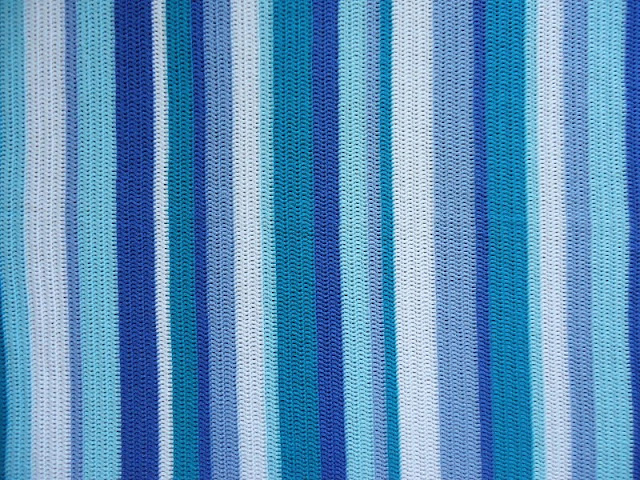 Looking for inspiration and ideas for a cute and easy stripy crochet blanket?  This is made in calm blue and green stripes, for a restful ocean feel.  Click to find out more details on the yarn and pattern used!