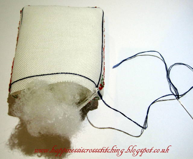 Filling a mattress pincushion with fibre fill for a cross stitched cottage design