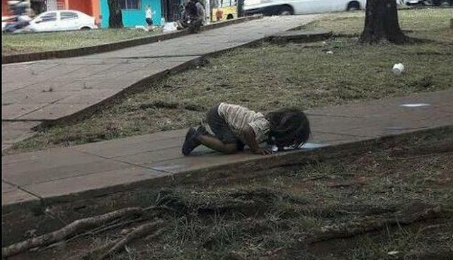 Φωτογραφία που σοκάρει: Κοριτσάκι πίνει νερό από λακκούβα σε πεζοδρόμιο