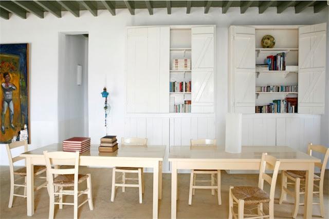 interior blanco con mesas de madera clara en casa de mykonos chicanddeco