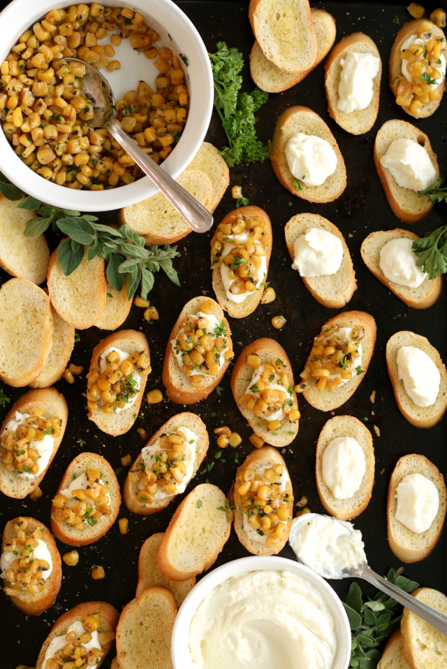 This Whipped Feta and Corn Crostini pairs pan-seared Libby's Whole Kernel Sweet Corn with salty feta cheese and fresh herbs in a delicious finger food appetizer that is perfect for parties! #sponsored #Cansgiving @LibbysTable