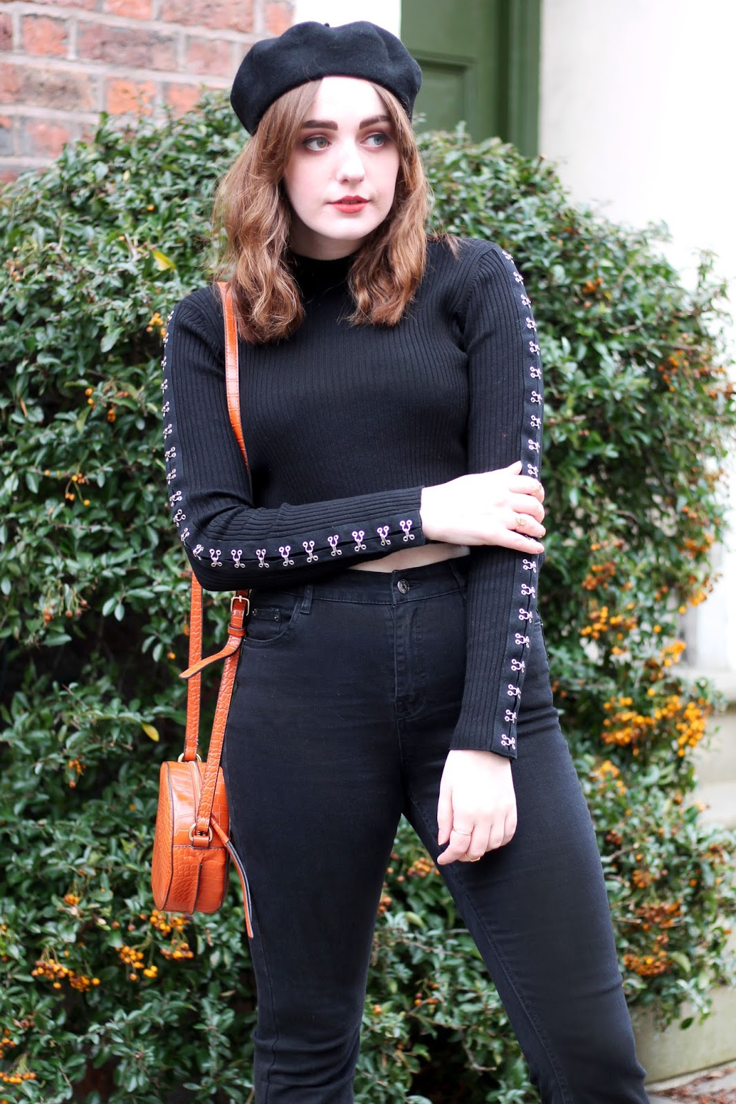 black beret, black top with hook and eye detailing, black kick flare jeans, orange circle bag