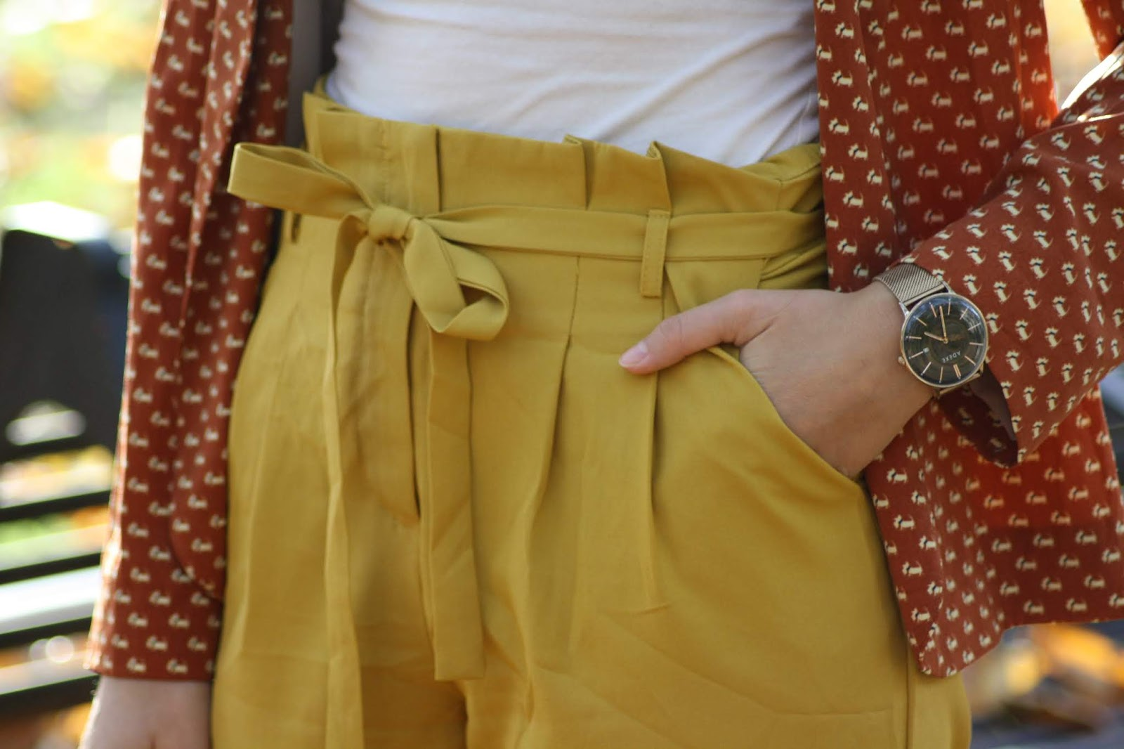 A close up of Abbey's yellow paperbag waist trousers and rose gold watch
