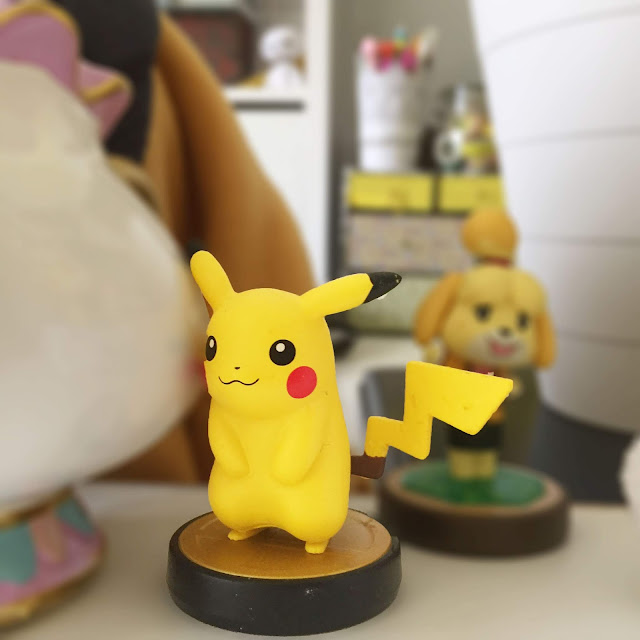 Pikachu standing next to isabelle of animal crossing. let's go pokemon review