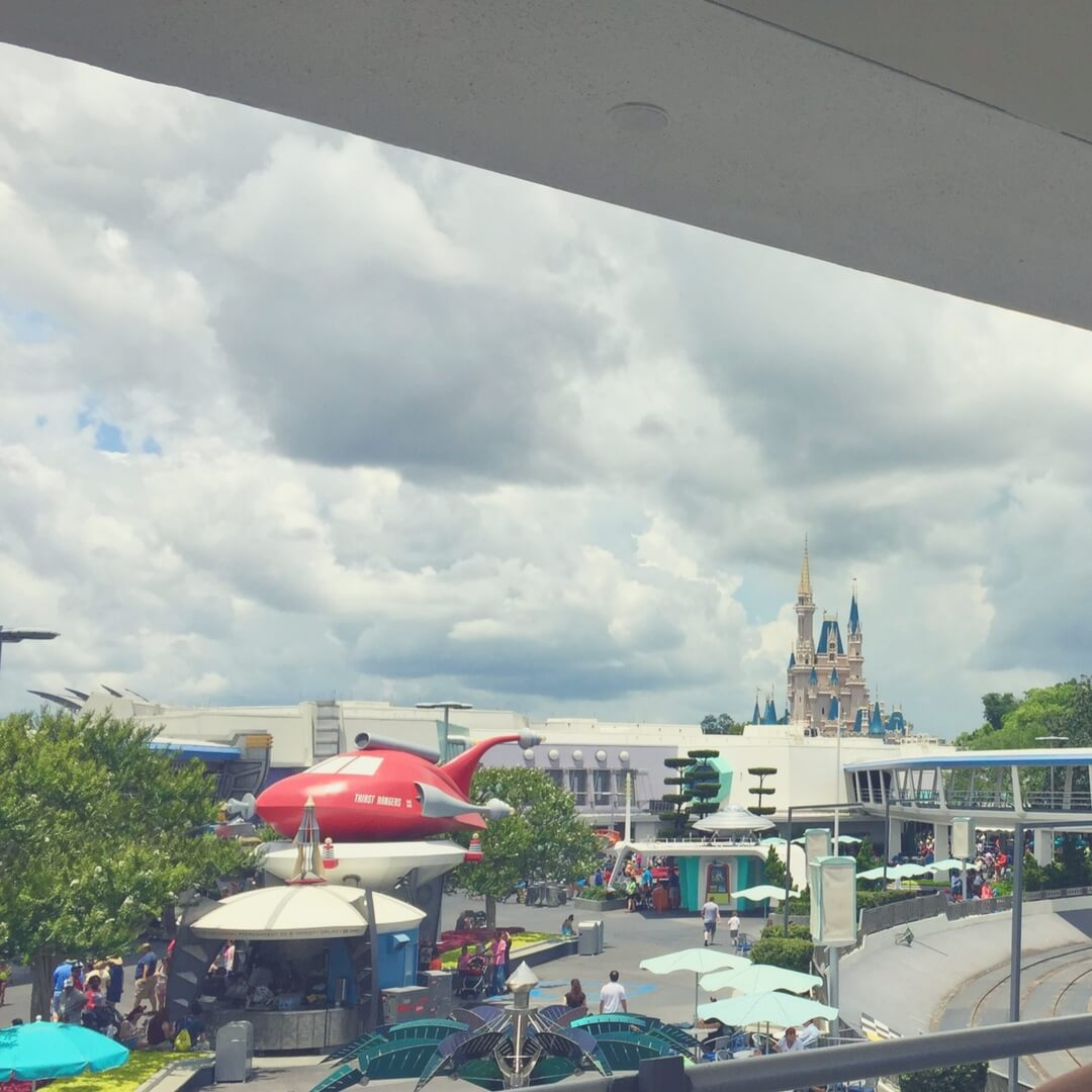 "A photo taken from the Transit Authority Peoplemover at Magic Kingdom. Cinderella's Castle is in the background, the tops of the spires poking up from behind a white building. A red rounded spaceship sits atop a drinks stand to the left of the photo, a queue of people standing in front of it. Trees are dotted around the area and people mill around. The sky is cloudy, but beautiful. Image for ""How to get a much-needed rest at Magic Kingdom"""
