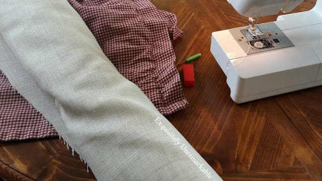 Linen fabric and red checked fabric next to sewing machine