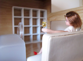 One-twelfth scale modern dolls' house doll sitting on a white sofa in a semi-empty modern miniature office, with a glass of wine in one hand.