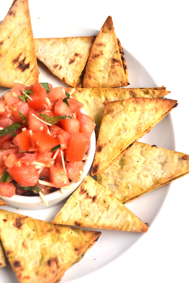 Bruschetta with Pesto Flatbread Chips make the perfect appetizer or snack with fresh tomatoes, garlic, Parmesan cheese and basil! The flatbread chips are thin, crispy and loaded with flavorful pesto. www.nutritionistreviews.com