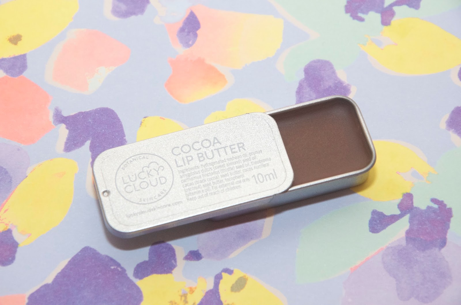 Vegan cocoa lip butter in silver tin on floral background