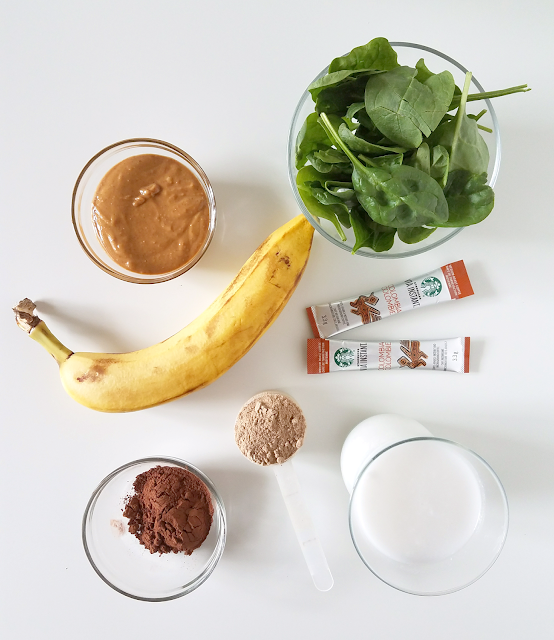 What makes this shake so delicious, nutritious and satisfying? A banana, spinach, peanut butter, cocoa powder, chocolate protein powder, instant coffee and milk.