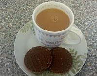 Cup of tea with two chocoloate biscuits on plate