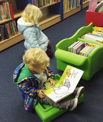 Toddler reading a good book in the library