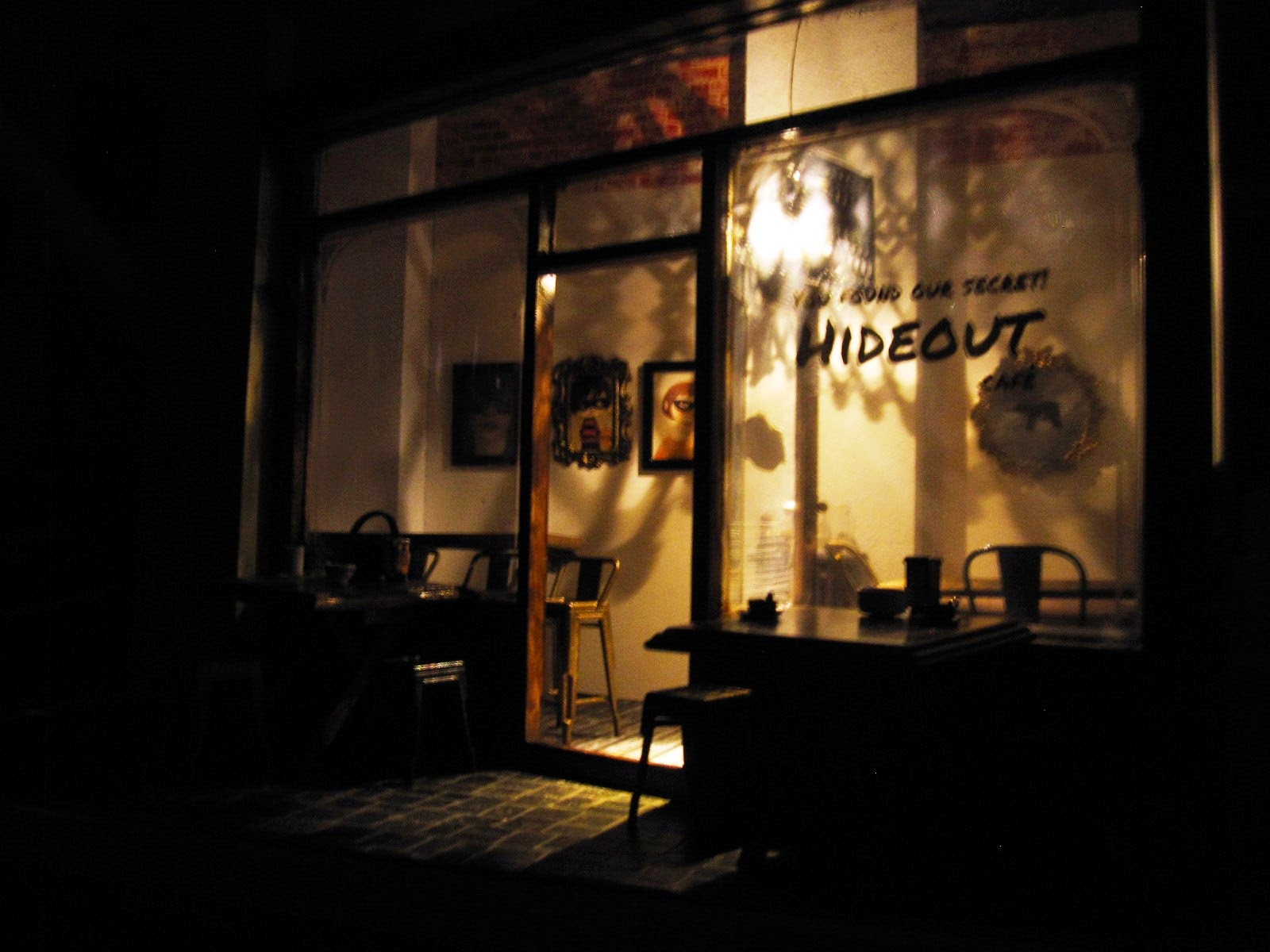 Exterior of a modern dolls' house miniature cafe at night, with the interior light up.