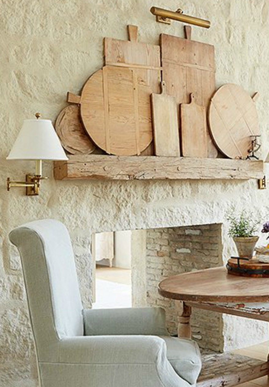 Charming and rustic bread boards lined up on a mantel of a limestone fireplace in a #farmhousekitchen with Old World style and #FrenchCountry style