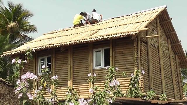 Casa construída com bambus segundo o método full scrib (troncos entrelaçados nos cantos)