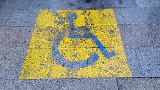 Señal de discapacidad pintada en el suelo. Fondo exterior azul, fondo interior negro y el símbolo de una persona en silla de color azul