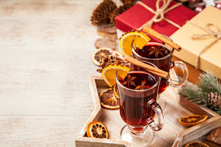 Two glass mugs of mulled cider, artfully presented with slices of clove-stuffed orange on the rim of the mugs, a cinnamon quill balanced across each, and star anise floating in the liquid.