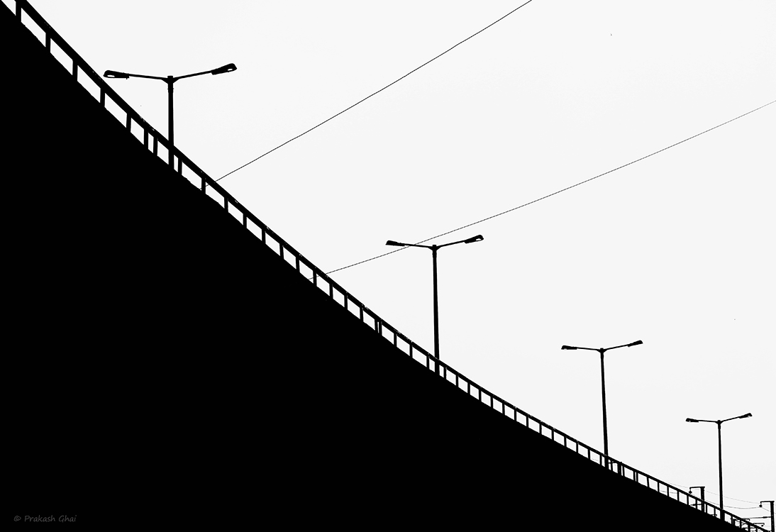 A black and white Minimalist Photo of Street lights in repetition on an over-bridge in Jaipur.