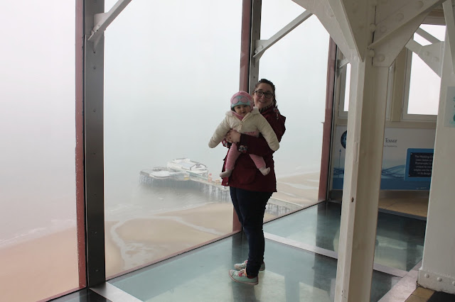 mother and baby stood on glass floor at Blackpool tower view overlooking the beach and pier