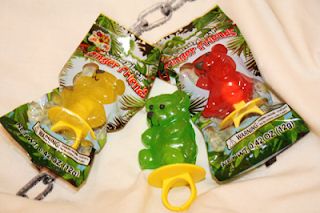 a red and a yellow candy bear ring in their packaging, and one green candy bear ring not in its packaging