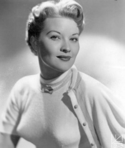 Portrait of Patti Page wearing tight sweater accenting bustline with bullet bra and worn with cardigan