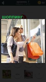 женщины во время шоппинга смотрят на витрину магазина