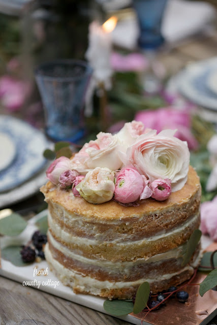 simple rustic cake topped with ranunculus and berries
