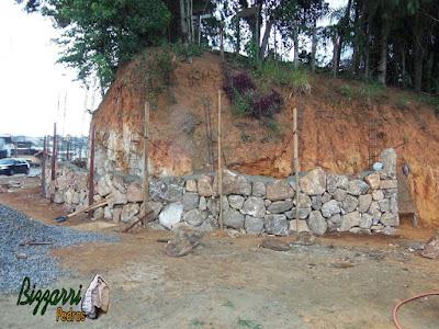 Execução do muro de pedra com pedras rústicas sendo tipo pedra moledo na face da frente do muro e o enchimento com pedra rachão. Muro de pedra na cidade de Joanópolis-SP com tipo de assentamento de pedra com junta seca sem massa.