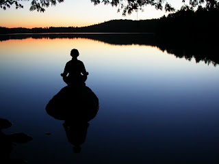 picture of person mediating on rock in a tranquil lake