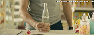 placing the coca cola bottle around his crotch to draw attention to the brand.