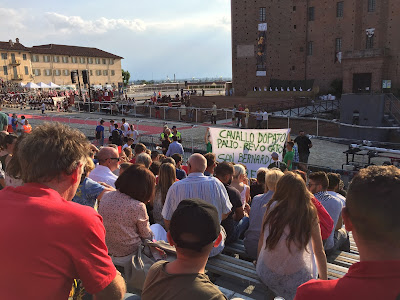 During the palio, fans making fun of San Bernardo and the horse-doping incident. The sign starts of: cavallo dopato...