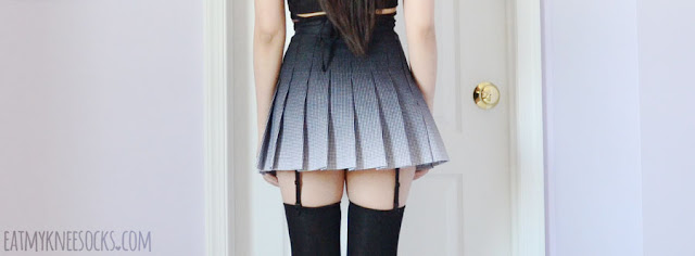 A monochromatic grunge-inspired outfit featuring the black and white ombre pleated American Apparel tennis skirt, garter lingerie and over-the-knee socks from Dresslink, a cropped faux suede lace-up top, and spiked leather black booties.