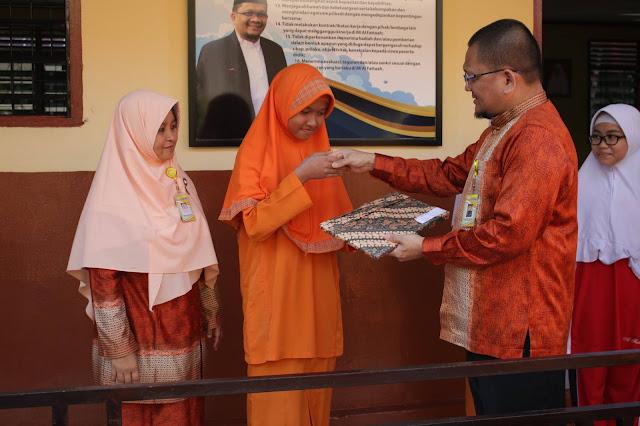 Kepala Sekolah MI Al-Fattaah Pekanbaru, Firdaus menyerahkan langsung hadiah kepada juara 1 lomba literasi