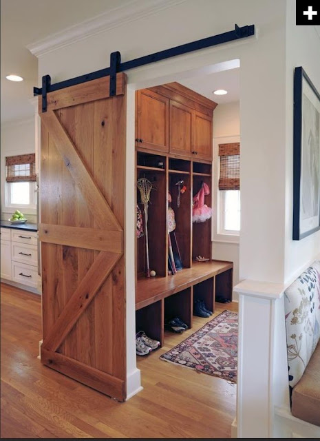 mud room with sliding barn door on natural wood.