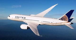 A foto mostra um avião B-787 com o nariz voltado à esquerda, em voo no céu claro. A aeronave é de grande porte com duas avantajadas turbinas, uma de cada lado, sustentadas na parte inferior das asas prateadas com aerodinâmica moderna e um enflechamento das asas mais acentuado nas extremidades finalizadas em pontas com inclinação leve para o alto. A fuselagem é branca, ao centro, janelinhas enfileiradas. Na cauda azul, o emblema da empresa representado por parte de uma esfera em fundo azul, com listras verticais em amarelo e linhas brancas horizontais semicirculares. De ponta a ponta, uma linha em dourado delineia o corpo do avião, inicia fina no nariz e finaliza larga, na cauda. Acima da porta principal, em letras azuis maiúsculas, o nome da empresa: United.