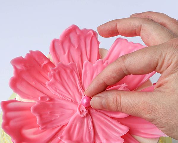 Για να ολοκληρώσετε, χρησιμοποείστε ένα στρογγυλό ζαχαρωτό, που θα το κολλήσετε στο κέντρο του λουλουδιού σας με λίγη λιωμένη σοκολάτα.