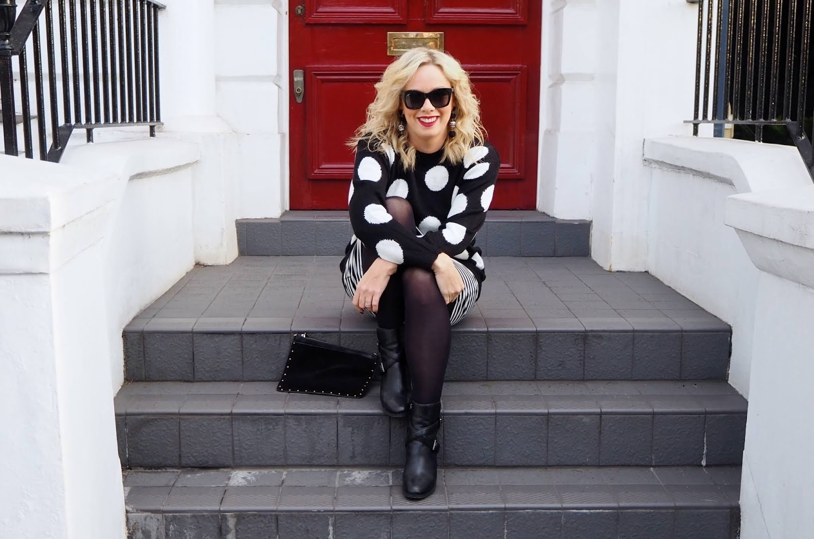 Black and white polka dot jumper with striped skirt, black tights, black boots, red lipstick and black wayfarer sunglasses