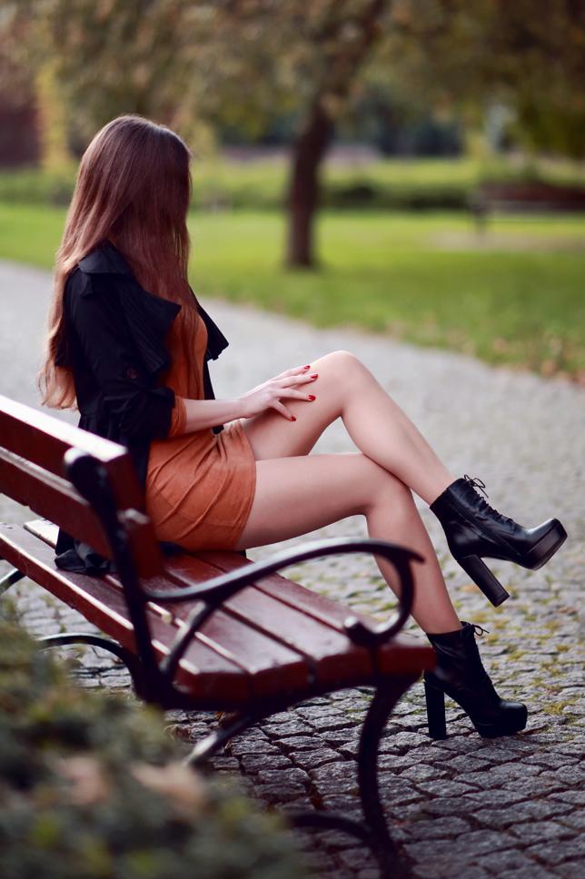 Czarny płaszcz, brązowa zamszowa sukienka, cieliste rajstopy i sznurowane botki na słupku
